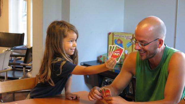 Mann mit Kind an Tisch, sie haben UNO-Karten in der Hand