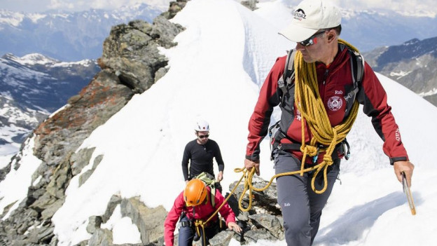 Bergführer mit Gruppe am Berg.