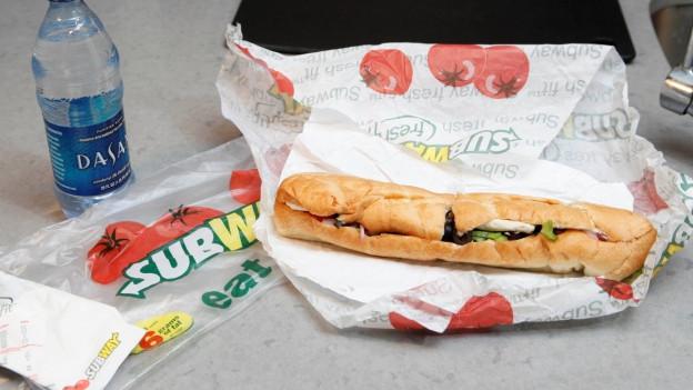 Sandwich auf Tisch, Subway-Papier ist darum gewickelt