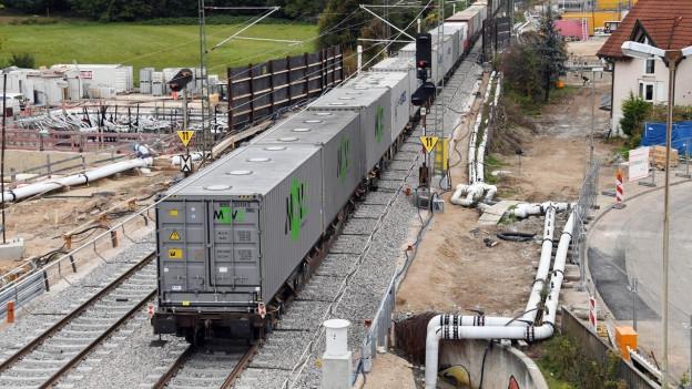 Güterzug, links und rechts Baustelle