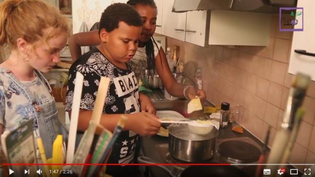Screenshot von Youtube-Video: Kinder vor einem Kochherd am Kochen