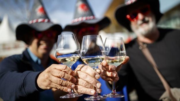 Drei Personen mit Weingläsern in der Hand