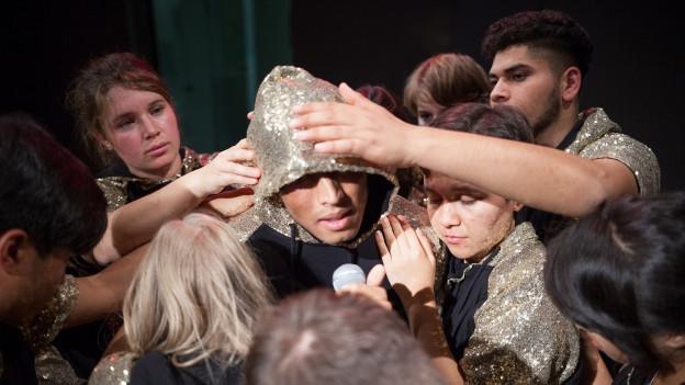 SchauspielerInnen auf der Bühne, Sie tragen Pulli mit goldenen Pailleten.