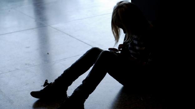 Mädchen sitzt am Boden