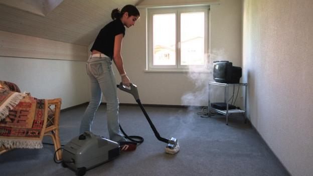 Frau reinigt Teppich mit Dampfgerät.