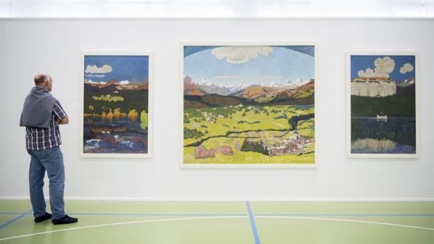Ein Besucher schaut auf ein Kunstgemälde mit Bergpanorama.