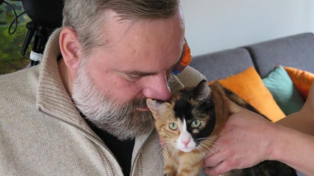 Stefan Csombo kann seine Katze nur mit fremder Hilfe streicheln.