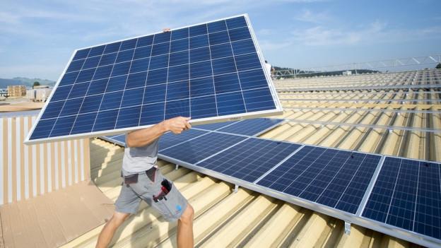 Mann transportiert ein Solarpanel auf einem Dach.