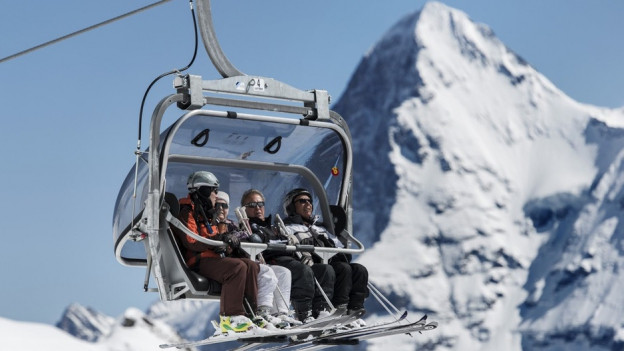Skifahrer auf Sesselbahn vor Eigernordwand.