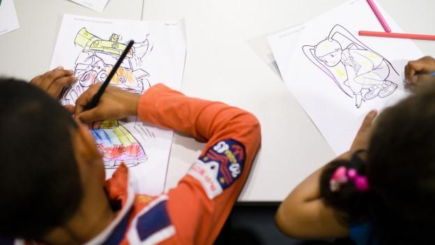 Zwei Kinder sitzen am Tisch und malen