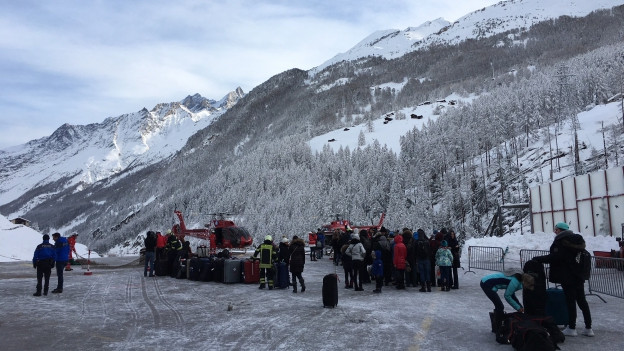Leute warten mit Koffern bei Helikoptern in Zermatt.