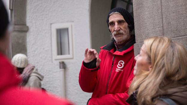 Ein Betroffener zeigt auf einem Rundgang Interessierten die Stadt, wie er sie sieht.