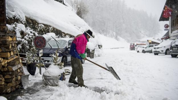 Mann schaufelt Schnee