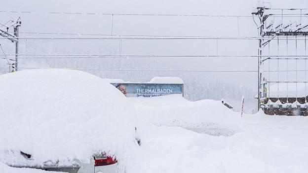 Verschneiter Bahnhof, dazu verschneites Werbeplakat