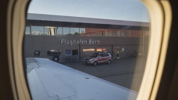 Blick aus einem Flugzeugfenster auf das Flughafengebäude Bern.