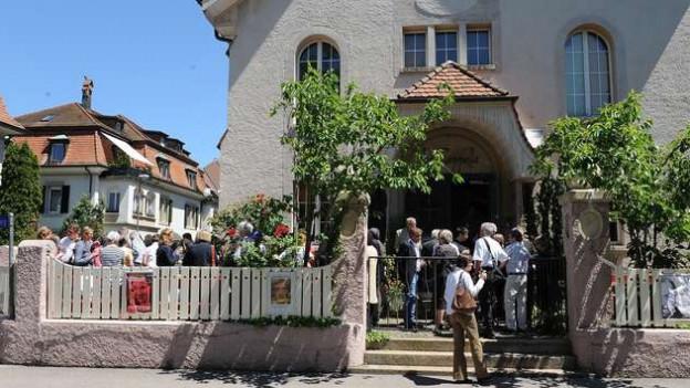 Blick auf Kirche mit vielen Leuten