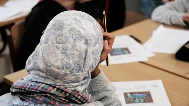 Junge Frau mit Kopftuch beugt sich über ein Lehrmittel.
