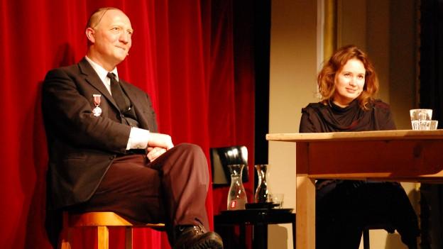 Beat Zeller und Patricia Kopatchinskaja am Tisch vor einem roten Vorhang