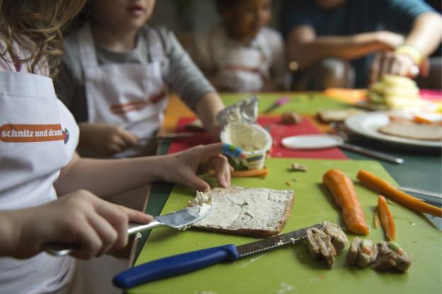 Kinder bereiten zusammen Gemüse vor