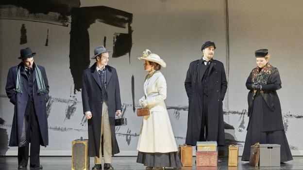Bühne mit Schauspielern, sie haben Koffer vor sich