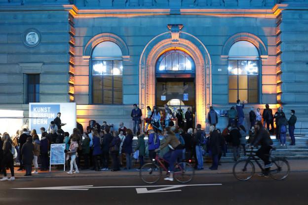 Menschen vor blau beleuchtetem Museum.