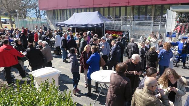 Menschen stehen in Gruppen beieinander vor dem Asylzentrum
