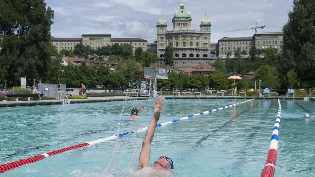 Schwimmer in Freibad, im Hintergrund Bundeshaus