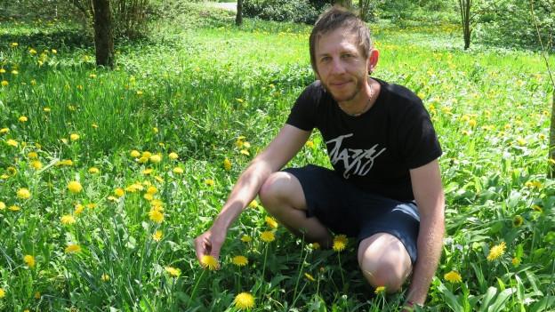 Adrian Möhl inmitten von Löwenzahnblumen