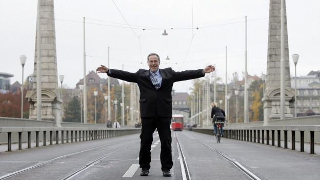 Mann auf Brücke mit ausgebreiteten Armen.