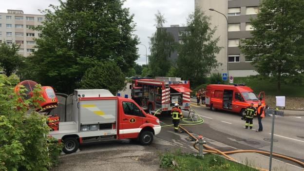 Feuerwehrautos vor Hochhäusern.