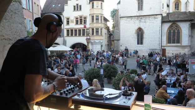 DJ am Plattenspieler vor Menschen auf Stadtplatz.