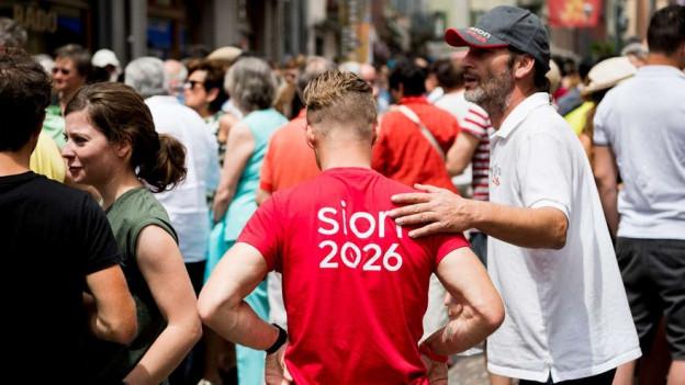 Mann in T-Shirt mit Aufschrift Sion 2026