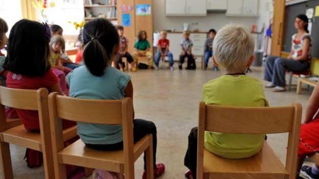 Kinder sitzen im Kindergarten im Kreis.