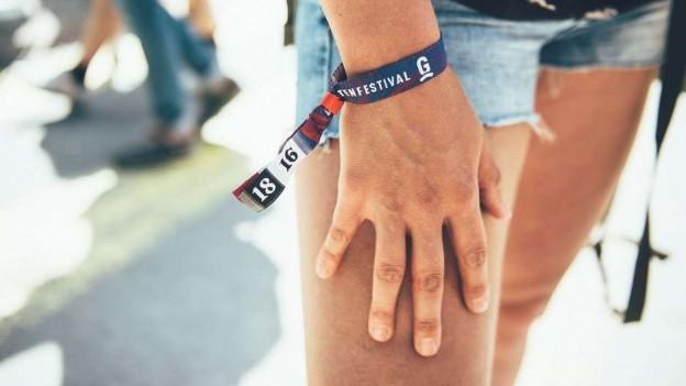 Frauenhand mit Festivalbändel.