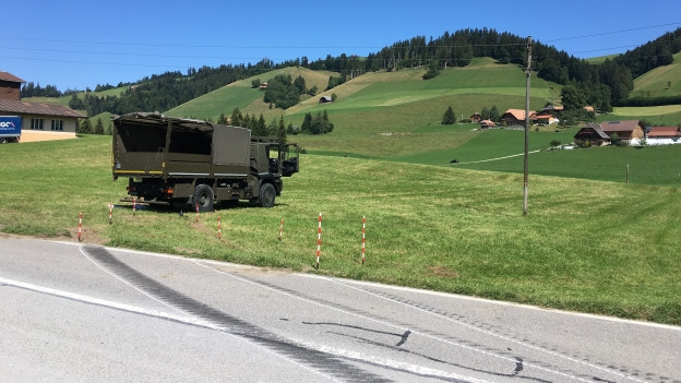 Bremsspuren auf Strasse, im Hintergrund ein Armeelastwagen.