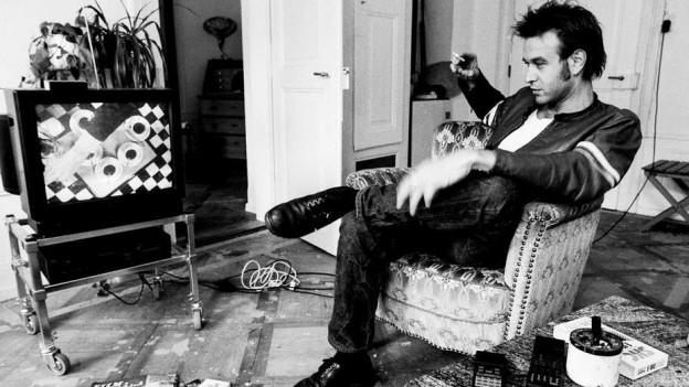 Mann mit Zigarette vor TV, Schwarzweiss-Aufnahme.