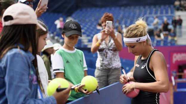 Tennisspielerin gibt Autogramme