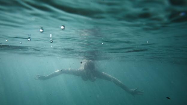 Frau schwimmt unter Wasser in der Aare
