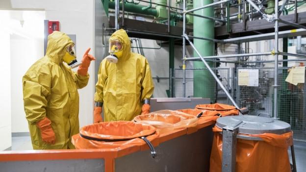 Zwei Mitarbeiter in gelben Schutzanzügen