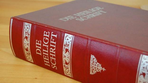 Bibel in rotem Umschlag auf einem Tisch.