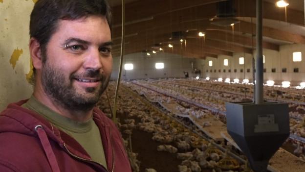 Mann im Vordergrund, Hühner in Halle im Hintergrund.