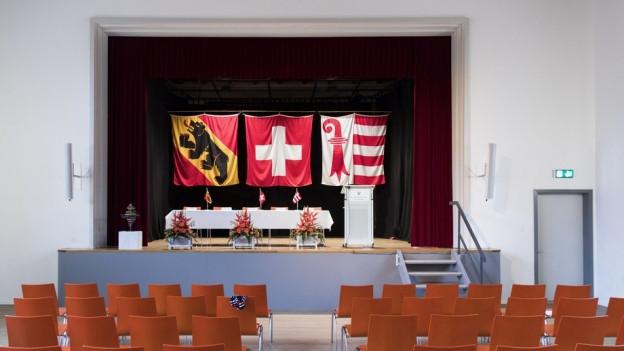 Berner und Jura-Flagge in einem Gemeindesaal, dazwischen die Schweizer Flagge.