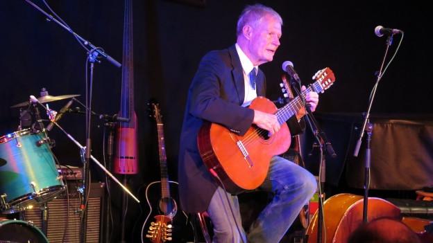 Mann mit Gitarre auf der Bühne.