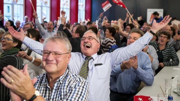 Viele sitzende Menschen klatschen und schwingen Walliser Fahnen. In der Bildmitte streckt ein lachender Mann mit Krawatte beide Hände in die Luft.