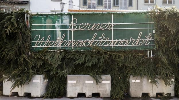 Die Leuchtschrift «Berner Weihnachtsmarkt», am Boden stehen graue Betonelemente unter Tannenzweigen.