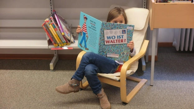 Junge Leseratte in der Bibliothek.