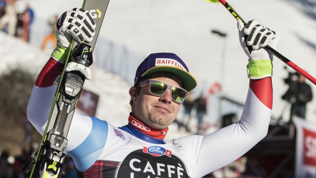 Portrait Beat Feuz mit Sonnenbrille und Skis in der Hand