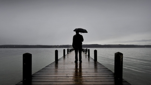 Mann mit Schirm auf Pier vor See.