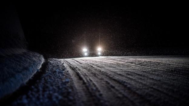 Auto nachts auf verschneiter Strasse