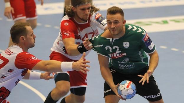 Drei Handballspieler auf dem Feld, sie zerren sich gegenseitig an den Leibchen.